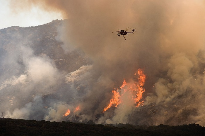700px-FEMA_-_33364_-_A_helicopter_drops_water_on_the_wildfire_in_California